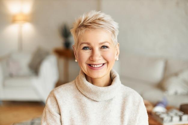 Feche a imagem de uma mulher feliz, bonita e elegante de cinquenta anos, vestindo um macacão aconchegante e aconchegante, brincos de pérola e um penteado curto e elegante, sentada na sala de estar de bom humor