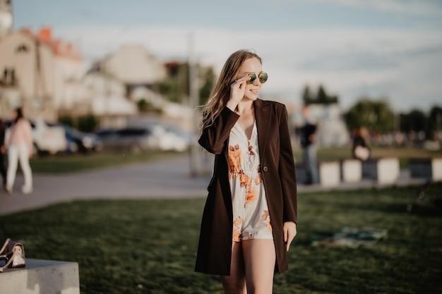 Feche a imagem de uma mulher feliz com roupas de óculos escuros posando de lado ao ar livre