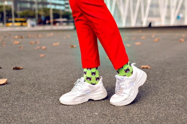 Feche a imagem de uma mulher hippie posando no outono, calças vermelhas, meias impressas na moda engraçadas e tênis grandes brancos.