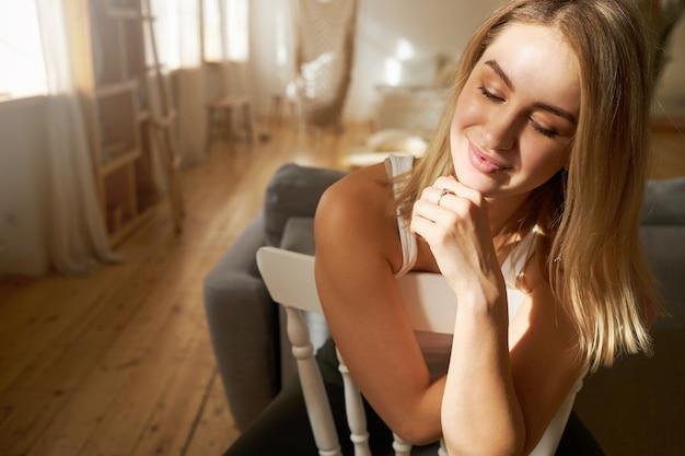 Feche a imagem de uma mulher jovem e atraente com lábios grandes e cabelos lisos loiros, sentada na cadeira com a mão no queixo, sorrindo misteriosamente, com uma expressão facial sonhadora