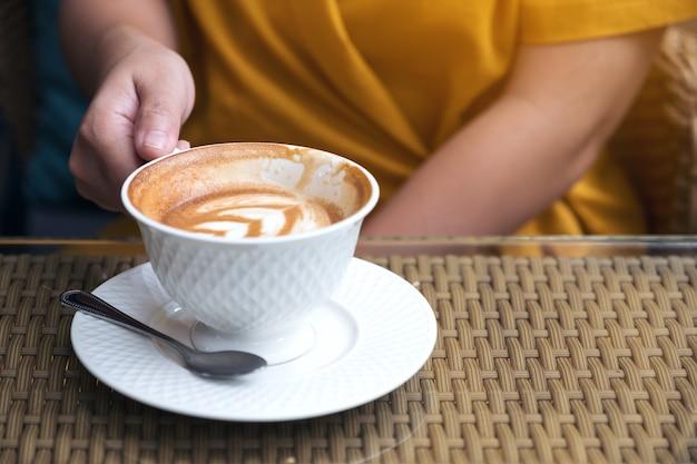 Feche a imagem de uma mulher segurando uma caneca de café branca no café