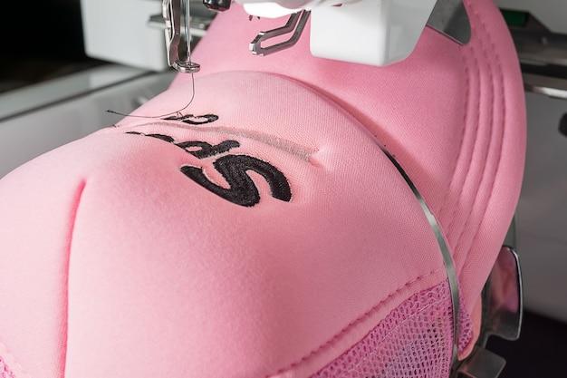 Feche a imagem do boné rosa e máquina de bordar