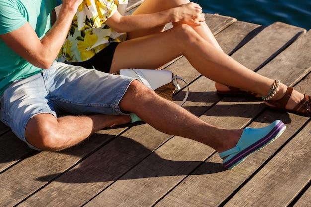 Feche a imagem do casal sentado no cais em um encontro romântico, concentre-se nas pernas.