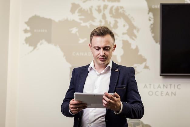 Feche a imagem do homem de negócios, segurando um tablet digital, retrato de jovem bonito, trabalhando com o tablet no escritório. empresário inteligente e confidentes, segurando o touch pad com infográficos