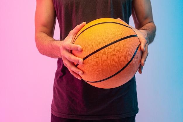 Feche a imagem do homem segurar a bola de basquete nas mãos. cara usa camiseta sem mangas. isolado em fundo azul e rosa. sessão de estúdio