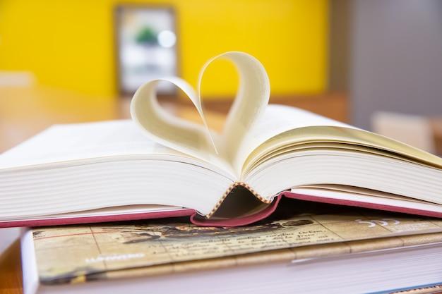 Feche a imagem do livro em forma de coração em cima da mesa na sala da biblioteca.