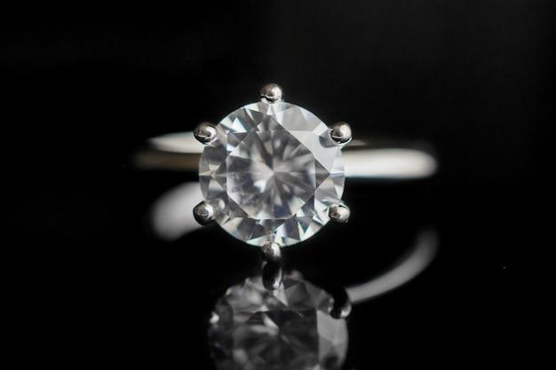 Feche a joia do anel de diamante com reflexo no fundo preto