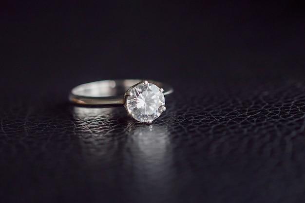 Feche a joia do anel de diamante na superfície de couro preto