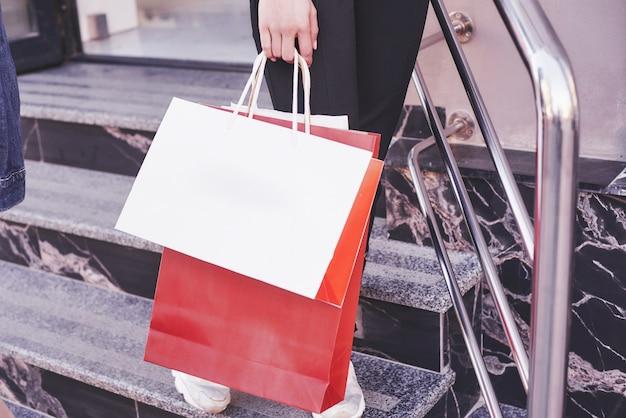 Feche a jovem carregando sacolas de compras enquanto caminha nas escadas, depois de visitar as lojas.