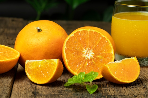 Feche a laranja cortada ao meio com a laranja em fatias e um copo de suco de laranja na mesa de madeira.