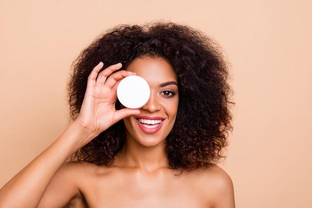 Feche a linda e incrível modelo de pele escura apresentando um creme facial diário aconselhando