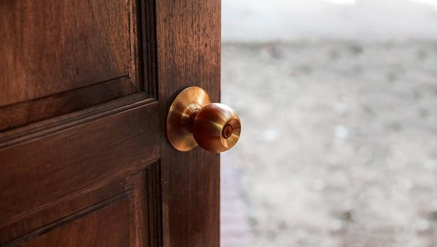Feche a maçaneta de cobre na porta de madeira para proteger o vírus do toque da mão para abrir a porta
