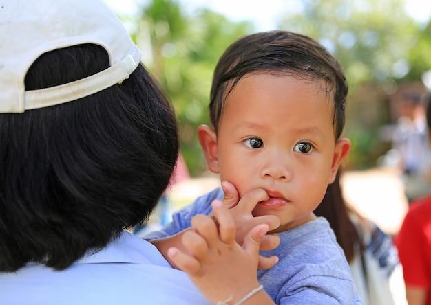 Feche a mãe asiática, carregando seu filho com chupar dedo na boca.