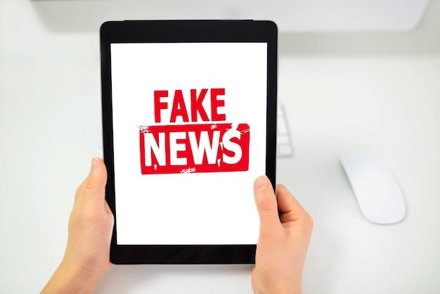 Feche a mão adulta segurando um tablet digital com o texto e o símbolo de notícias falsas na tela.