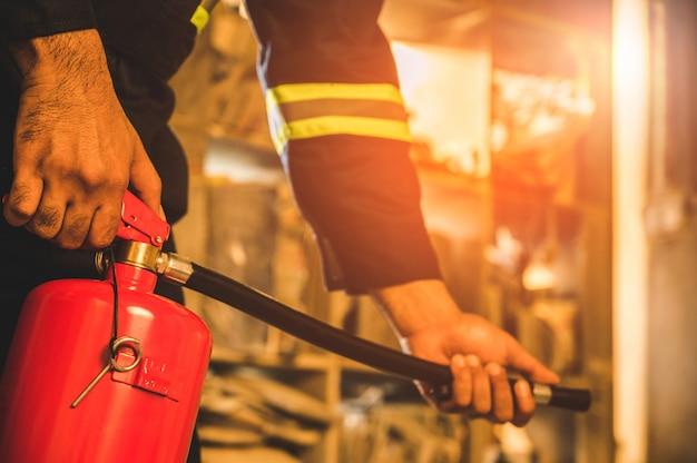 Feche a mão bombeiro usando extintor de combate.