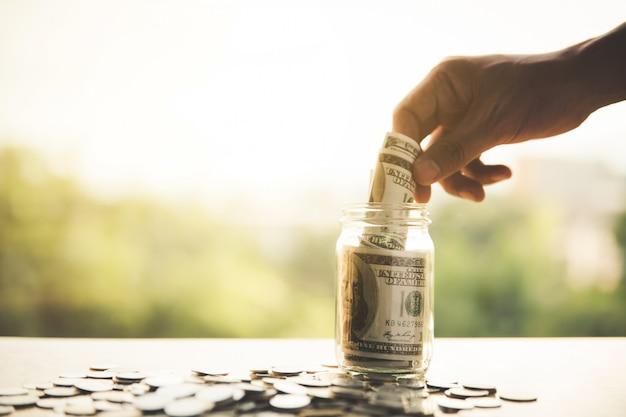 Feche a mão colocando notas em garrafa de vidro. negócio, finanças, poupança ou gestão