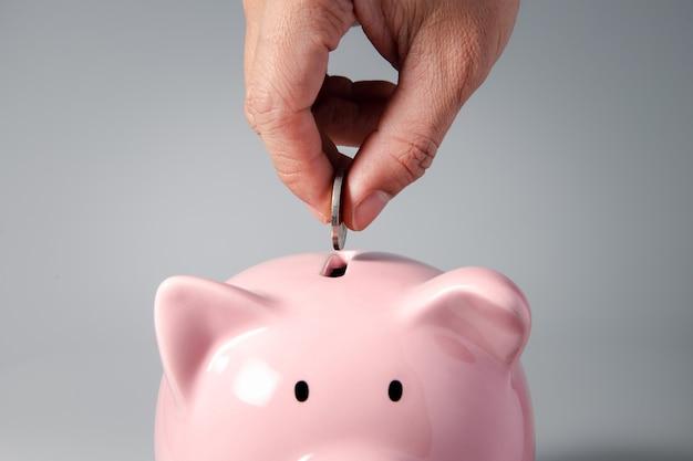 Feche a mão colocando uma moeda no cofrinho para finanças
