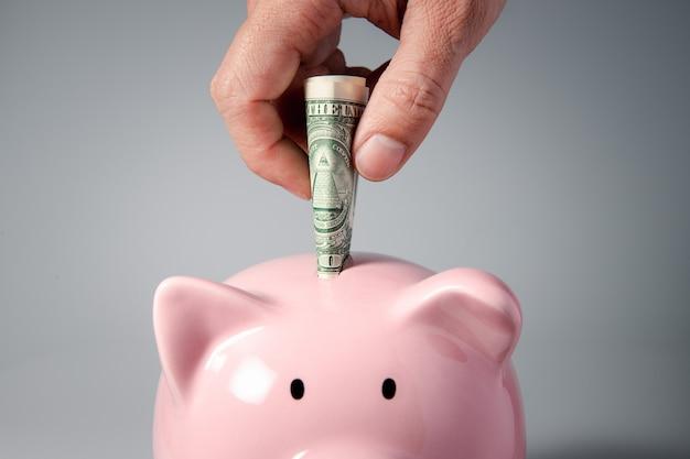 Feche a mão colocando uma nota no cofrinho para finanças