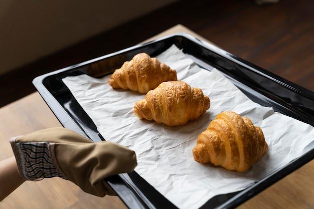 Feche a mão com a bandeja de croissants