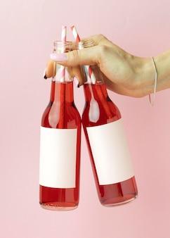 Feche a mão com garrafas de bebida