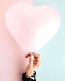 Feche a mão com um balão em forma de coração