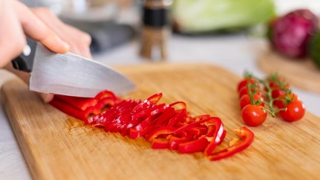 Feche a mão cortando pimenta com faca