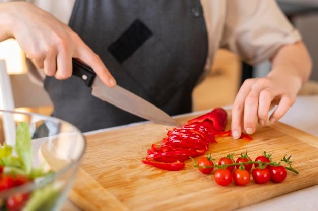 Feche a mão cortando pimenta