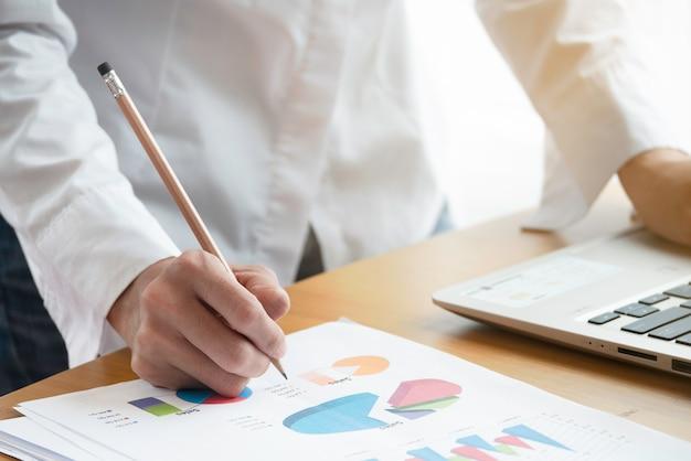 Feche a mão da empresária, trabalhando com dados de negócios e documento.