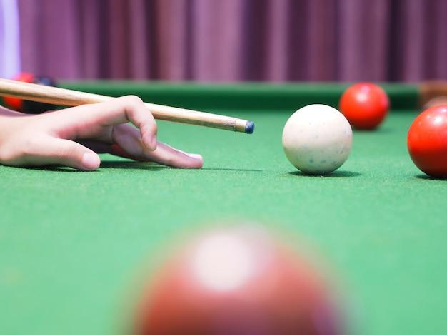 Feche a mão da garota na mesa verde, jogando bolas de bilhar.