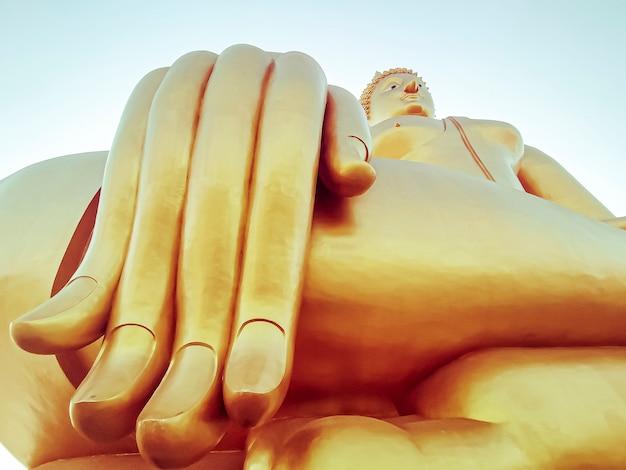 Feche a mão da grande estátua de buda com céu azul em wat tha muang tailândia. as estátuas mais icônicas do buda dourado