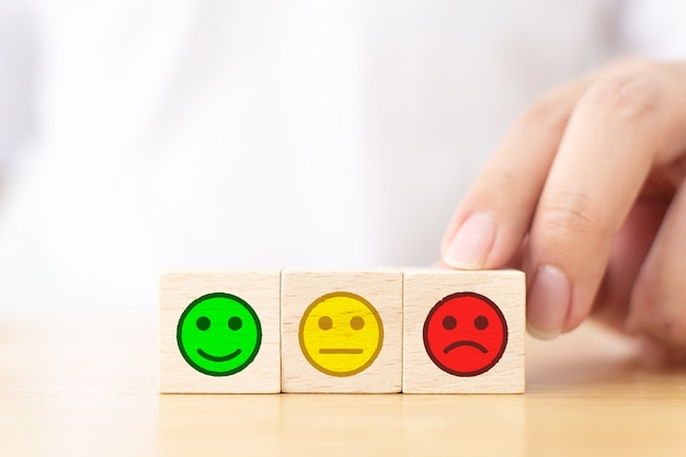 Feche a mão da imagem do cliente, escolha a placa de rosto triste em um bloco de cubo de madeira