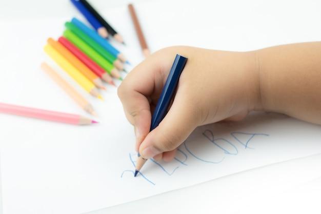 Feche a mão da menina com um lápis escrevendo palavras em inglês com a mão