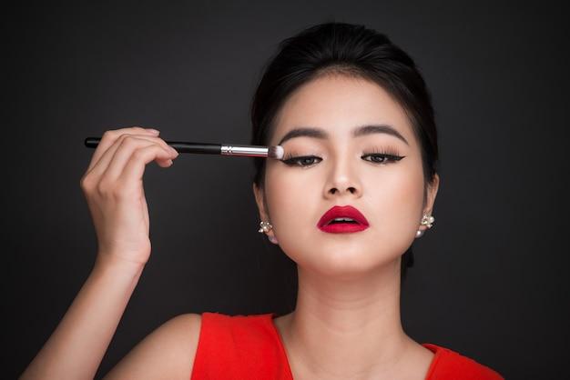 Feche a mão da mulher asiática, aplicando a sombra na pálpebra feminina.
