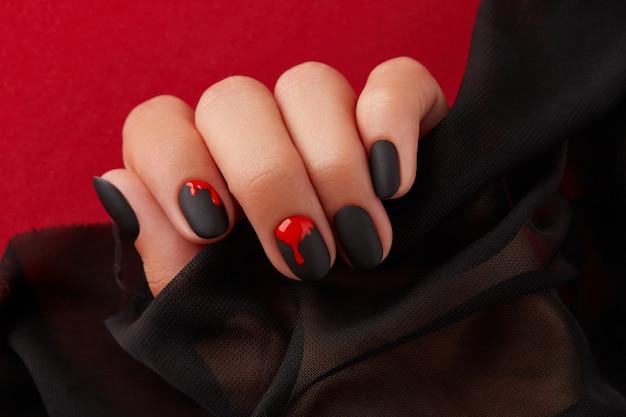 Feche a mão da mulher com manicure de halloween em fundo vermelho segurando o tecido