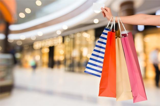 Feche a mão da mulher com muitas sacolas de compras e cartão de crédito