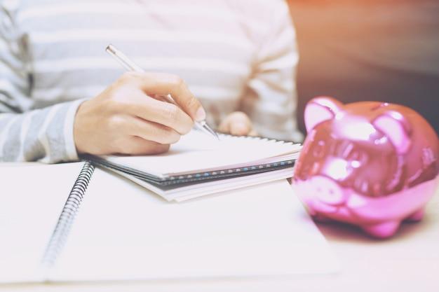 Feche a mão da mulher de negócios segurando uma caneta e abra o bloco de notas da página