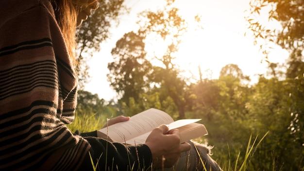 Feche a mão da mulher enquanto lê o livro.