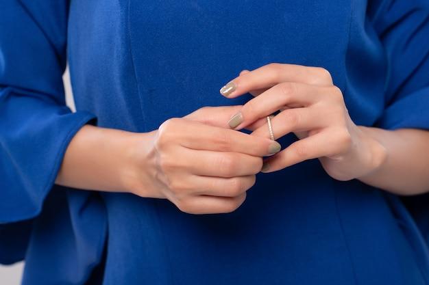 Feche a mão da mulher está decolando o anel de casamento. quebre meu conceito de coração e divórcio.