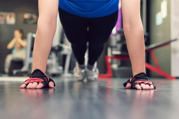 Feche a mão da mulher fazendo flexões no ginásio. treinando meninas no corredor. mãos enluvadas no chão em close-up. mitaines.