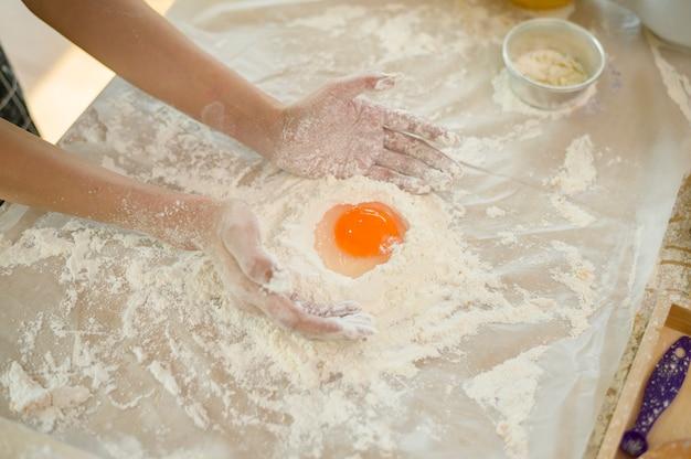 Feche a mão da mulher fazendo uma padaria