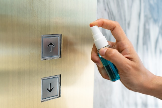Feche a mão da mulher que desinfecta o botão do elevador pulverizando álcool de uma garrafa. proteção contra vírus infecciosos, bactérias e germes, coronavirus / covid-19, conceito de cuidados de saúde.