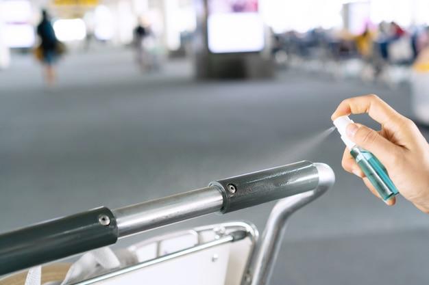Feche a mão da mulher que desinfeta o carrinho do aeroporto pulverizando álcool de uma garrafa, proteção contra vírus infeccioso, bactérias e germes. conceito de cuidados de saúde.