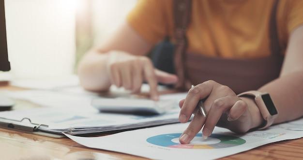 Feche a mão da mulher segurando a caneta e apontando para a papelada financeira com o diagrama da rede financeira.