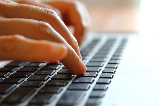 Feche a mão da mulher trabalhando com o laptop