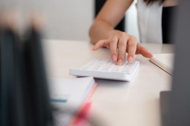 Feche a mão da mulher usando a calculadora e escreva, anote com calcular sobre o custo no escritório em casa.