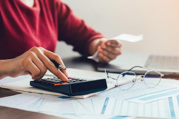 Feche a mão da mulher usando uma calculadora e a outra mão segura a conta com calcular