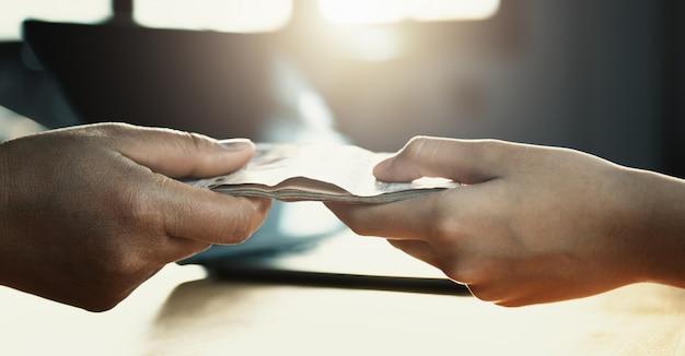Feche a mão dando dinheiro para o parceiro na mesa