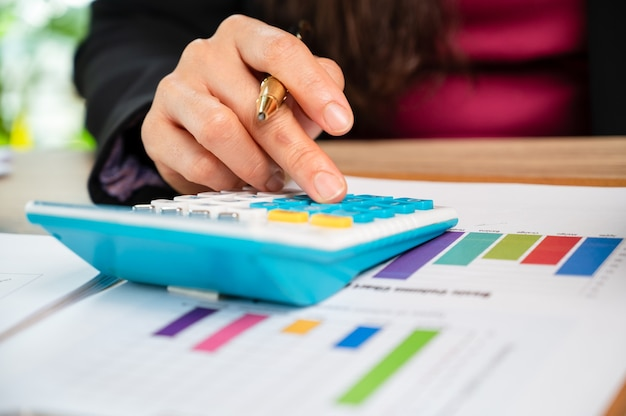 Feche a mão de businesswomann usando finanças domésticas de máquina de cálculo ou impostos sobre a máquina, conceitos de finanças e contabilidade,