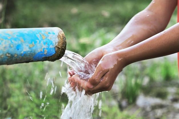 Feche a mão de crianças e respingo de gota de água no tubo