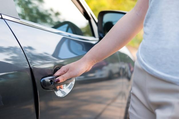 Feche a mão de mulher abrindo a porta do carro.